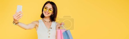 happy fashionable girl in sunglasses with shopping bags taking selfie on smartphone isolated on yellow