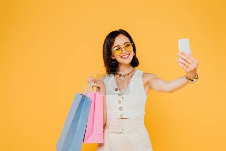 Photo for Happy fashionable girl in sunglasses with shopping bags taking selfie on smartphone isolated on yellow - Royalty Free Image