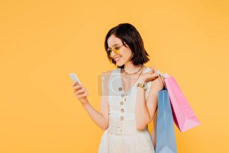 Photo pour Fille à la mode de sourire dans des lunettes de soleil avec des sacs à provisions utilisant le smartphone isolé sur le jaune - image libre de droit