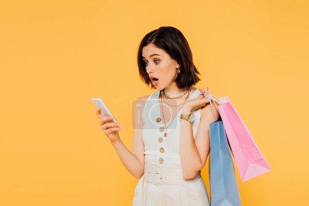 Schockiertes Mädchen mit Einkaufstüten spricht auf Smartphone