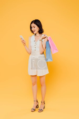 Photo for Excited girl with shopping bags talking on smartphone isolated on yellow - Royalty Free Image