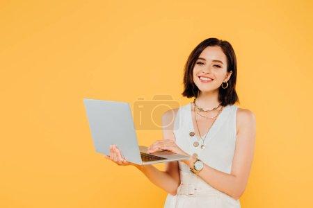 Lächeln elegante Mädchen mit Laptop isoliert auf gelb