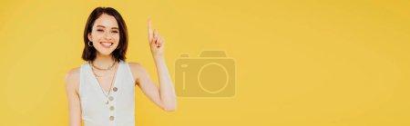 Photo pour Tir panoramique de la fille élégante de sourire affichant le geste d'idée d'isolement sur le jaune - image libre de droit