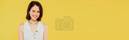 Photo pour Tir panoramique de sourire élégant clin d'un an isolé sur le jaune - image libre de droit
