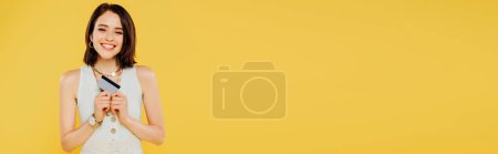 Photo for Panoramic shot of smiling elegant girl holding credit card isolated on yellow - Royalty Free Image