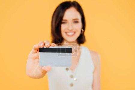 Photo pour Foyer sélectif de sourire élégante fille tenant carte de crédit isolé sur jaune - image libre de droit