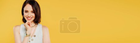Photo for Panoramic shot of smiling elegant girl with hand on chin isolated on yellow - Royalty Free Image
