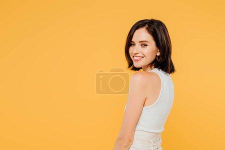 Foto de Sonrisa chica elegante mirando a la cámara aislada en amarillo - Imagen libre de derechos