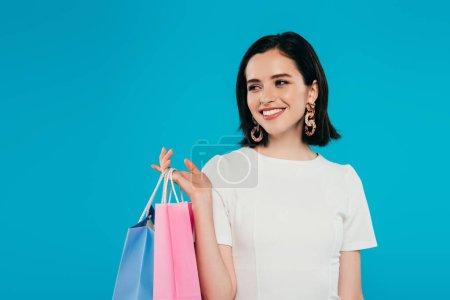 Foto de Sonriente mujer elegante en vestido con bolsas de compras mirando hacia otro lado aislado en azul - Imagen libre de derechos