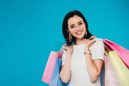 Photo pour Femme élégant de sourire dans la robe avec des sacs à provisions d'isolement sur le bleu - image libre de droit