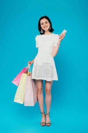 Photo pour Vue pleine longueur de femme élégante de sourire dans la robe avec des sacs à provisions et le smartphone d'isolement sur le bleu - image libre de droit