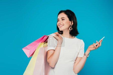 Photo pour Femme élégante souriante en robe avec des sacs à provisions et smartphone regardant loin isolé sur bleu - image libre de droit