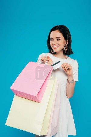 Photo pour Femme élégant de sourire dans la robe avec des sacs à provisions retenant la carte de crédit d'isolement sur le bleu - image libre de droit