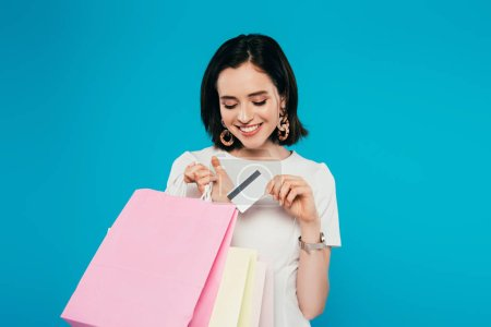 Photo for Smiling elegant woman in dress with shopping bags holding credit card isolated on blue - Royalty Free Image