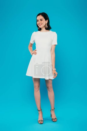 Photo pour Vue pleine longueur de femme élégante de sourire dans la robe avec la main sur la hanche d'isolement sur le bleu - image libre de droit