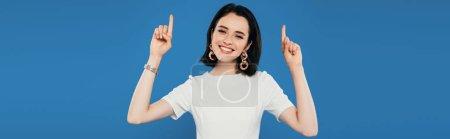 Photo pour Plan panoramique de sourire élégante fille pointant avec les doigts vers le haut isolé sur bleu - image libre de droit