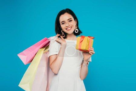lächelnde elegante Frau im Kleid mit Einkaufstaschen und Geschenkschachtel auf blauem Grund