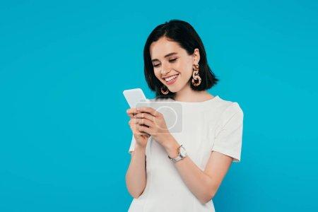 Photo pour Femme élégante souriante en robe en utilisant smartphone isolé sur bleu - image libre de droit