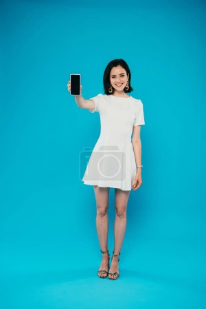 full length view of smiling elegant woman in dress holding smartphone with blank screen isolated on blue