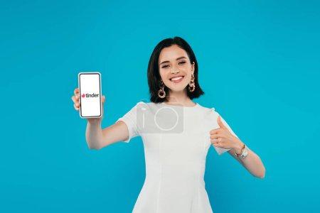Photo pour Kiev, Ukraine - 3 juillet 2019: femme élégante souriante dans la robe retenant le smartphone avec le logo de tinder et affichant le pouce vers le haut d'isolement sur le bleu - image libre de droit
