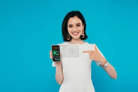 Photo pour Femme élégante souriante en robe pointant du doigt le smartphone avec l'application d'analyse marketing isolé sur bleu - image libre de droit