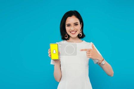 Photo pour Kiev, Ukraine - 3 juillet 2019: femme élégante souriante en robe pointant du doigt le smartphone avec le logo snapchat isolé sur le bleu - image libre de droit