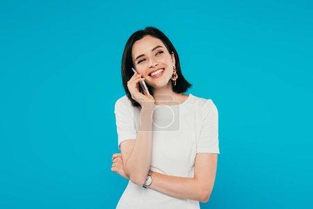 lächelnde elegante Frau im Kleid, die auf dem Smartphone spricht und isoliert auf blauem Grund wegschaut