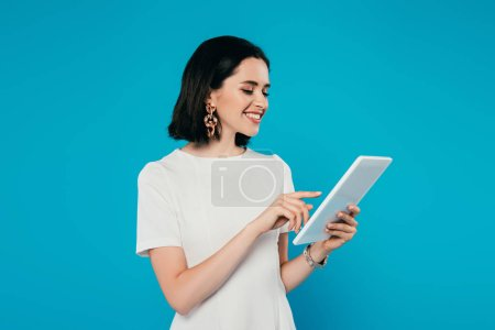 Photo for Smiling elegant woman in dress using digital tablet isolated on blue - Royalty Free Image