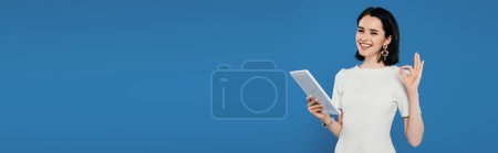 Photo for Panoramic shot of smiling elegant woman holding digital tablet and showing okay sign isolated on blue - Royalty Free Image