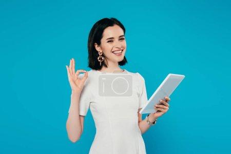 Photo pour Femme élégante souriante tenant tablette numérique et montrant signe OK isolé sur bleu - image libre de droit