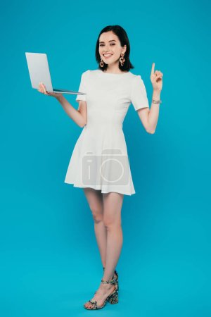 full length view of smiling elegant woman holding laptop and showing idea gesture isolated on blue