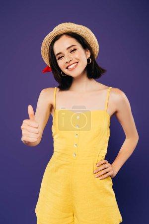Photo pour Fille souriante en chapeau de paille avec la main sur la hanche montrant pouce vers le haut isolé sur violet - image libre de droit