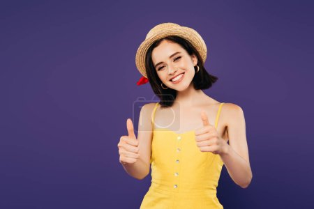 Photo for Smiling girl in straw hat showing thumbs up isolated on purple - Royalty Free Image