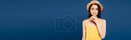 Photo pour Plan panoramique de fille en chapeau de paille montrant le signe shh isolé sur bleu - image libre de droit