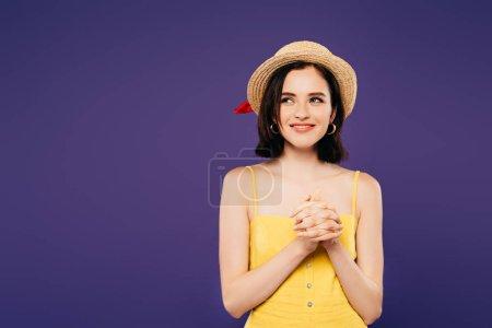 Photo pour Fille souriante en chapeau de paille avec les mains serrées regardant loin isolé sur violet - image libre de droit