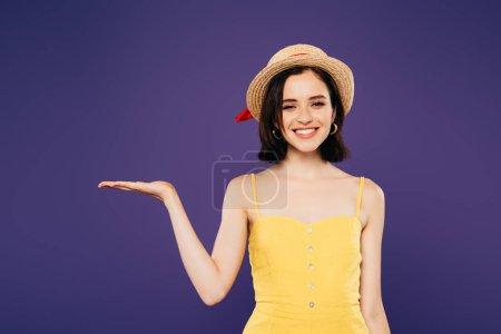 Lächelndes Mädchen mit Strohhut, das mit der Hand auf Lila zeigt