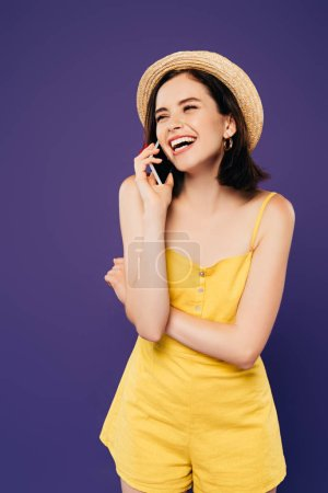 Photo pour Fille heureuse dans le chapeau de paille parlant sur le smartphone et riant isolé sur le pourpre - image libre de droit