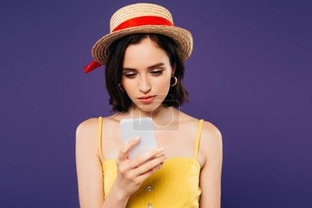 Photo pour Fille en chapeau de paille en utilisant smartphone isolé sur violet - image libre de droit