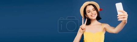Photo pour Fille de sourire dans le chapeau de paille prenant le selfie sur le smartphone et affichant le signe de paix d'isolement sur le bleu - image libre de droit