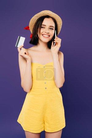 Lächelndes Mädchen mit Strohhut, das auf dem Smartphone spricht und Kreditkarte isoliert auf lila hält