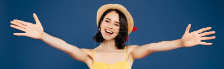 panoramic shot of smiling pretty girl in straw hat with open arms isolated on blue