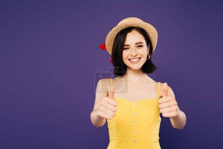 sonriente chica bonita en sombrero de paja mostrando pulgares hacia arriba aislado en púrpura