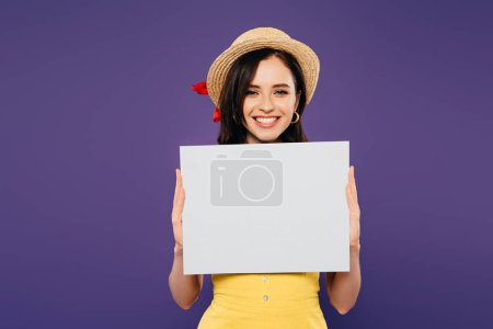 Photo for Happy girl in straw hat holding empty board isolated on purple - Royalty Free Image