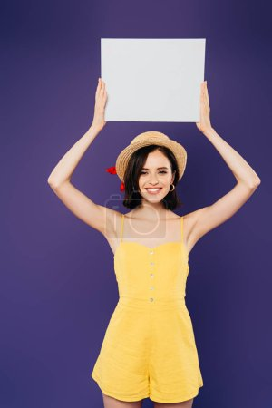 Photo for Happy girl in straw hat holding empty board above head isolated on purple - Royalty Free Image
