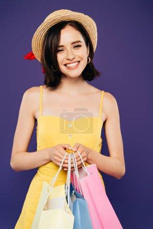 Photo pour Fille souriante dans un chapeau de paille tenant des sacs à provisions isolés sur violet - image libre de droit