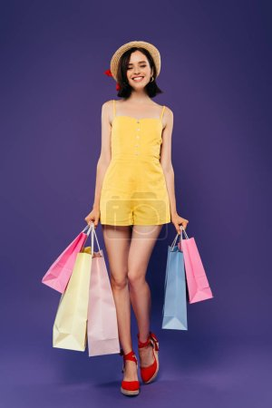 Photo for Full length view of smiling girl in straw hat with shopping bags isolated on purple - Royalty Free Image