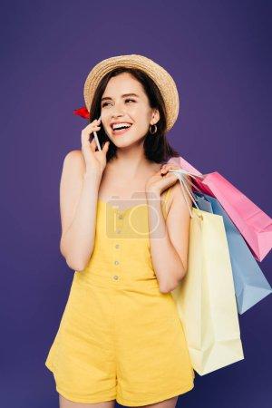 Photo pour Fille souriante dans un chapeau de paille avec des sacs à provisions parler sur smartphobne isolé sur violet - image libre de droit