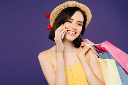 Photo pour Fille souriante dans un chapeau de paille avec des sacs à provisions parlant sur smartphone isolé sur violet - image libre de droit