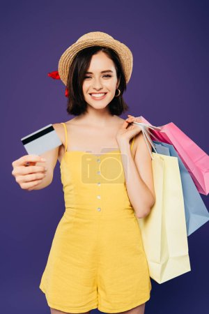 Photo pour Fille de sourire dans le chapeau de paille avec des sacs à provisions présentant la carte de crédit d'isolement sur le pourpre - image libre de droit