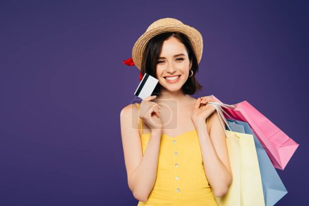 Photo pour Fille de sourire dans le chapeau de paille avec des sacs à provisions retenant la carte de crédit d'isolement sur le pourpre - image libre de droit